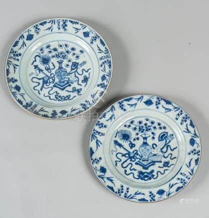 Deux assiettes en porcelaine à décor en bleu sous couverte d'un vase fleuri et