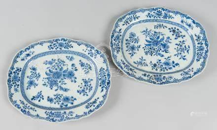Paire de plats ovales à bords chantournés à décor fleuri en bleu sous couverte