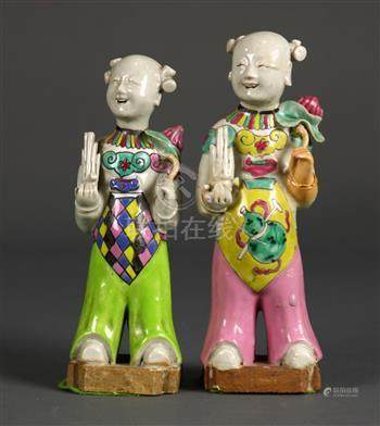 Pair of Chinese porcelain figures, each in the form of a child holding a sheng flute and a lotus