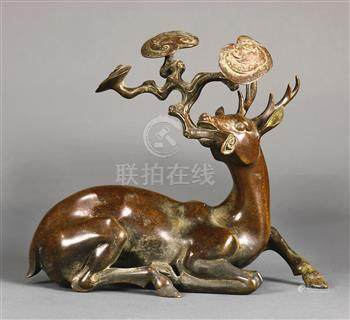 Chinese bronze sculpture of a deer, the recumbent animal clasping a large lingzhi sprig in its