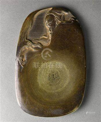Chinese ink stone, low relief carved as a seated scholar, reversed with inscription marked '