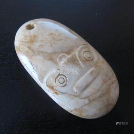 Amulette ovale au masque chamanique. Jade néphrite. L 7.5cm. Chine du sud est,