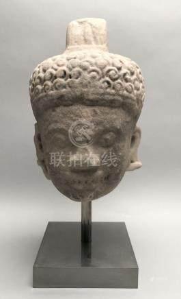 Tête de divinité surmontée d'une coiffe, en grès rose. Cambodge, art Khmer, d'é