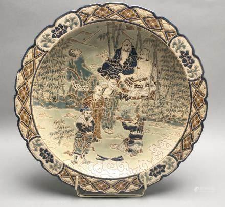 Grand plat rond en grès porcelaineux à décor émaillé polychrome de personnages