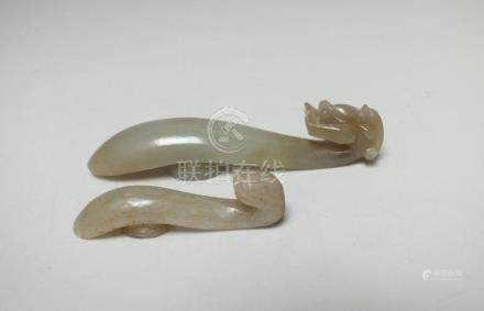 TWO CHINESE CELADON JADE BELT HOOKS, of plain form with carved mythical dragon head to one end,