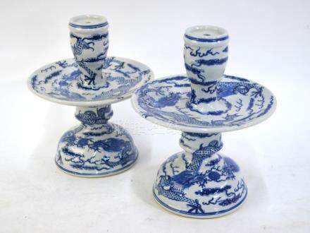 A pair of Chinese blue and white, candle or joss-stick holders; each one with circular plate