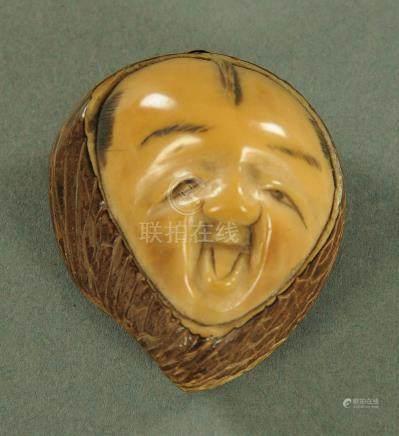 A Japanese carved Tagua nut Netsuke, circa 1900, carved as a yawning Daruma, signed verso, 4.