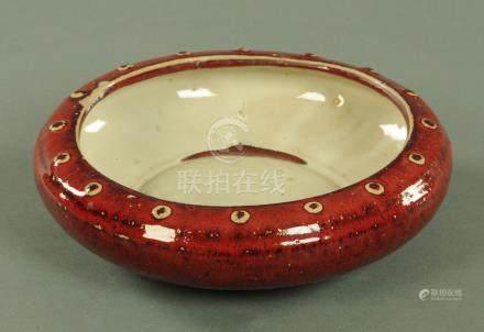 A Chinese Sang de Boeuf glazed bowl, Qing dynasty, of squat circular form,