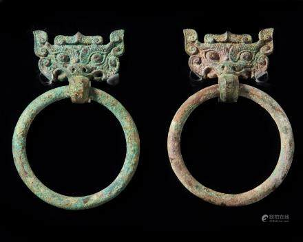 A pair of Chinese bronze taotie mask fittings with loose-ring handles