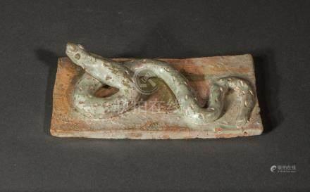 Brique décorative de sanctuaire enluminée en haut relief d'un serpent sinueux.