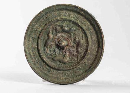 Miroir circulaire  en bronze décoré d'un fond de motifs zoomorphes et d'une bos