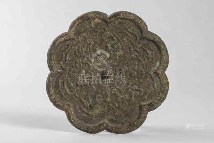 Miroir polylobé en bronze décoré  d'un fond de motifs floraux et d'une bossette