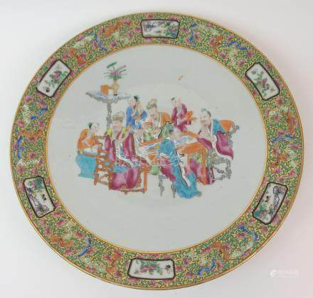 A CANTON CHARGER painted with scholars and attendants at a table within a dense gilt and