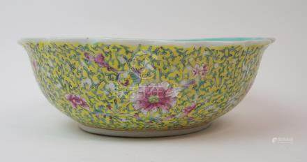 A CHINESE YELLOW GROUND FRILLED BOWL exterior with peonies and scrolling foliage, Qianlong seal mark