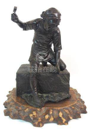 A JAPANESE BRONZE OF A STONE MASON standing over a large stone block with hammer and chisel,