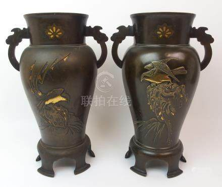 A PAIR OF JAPANESE BRONZE TWO-HANDLED BALUSTER VASES decorated with peonies issuing from rockwork