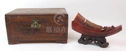 A CHINESE CARVED BUFFALO HORN SAMPAN with four figures and shelter on board resting on hardwood