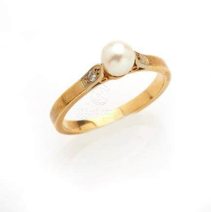 Bague en or jaune 18K (750/°°), ornée d une perle culture, épaulée par un diama
