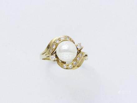 Bague en or 750 millièmes centrée d'une perle de culture épaulée et entourée de