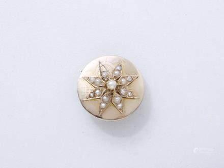 444/ Broche ronde en or 750 millièmes centrée d'une étoile rehaussée de demi-pe