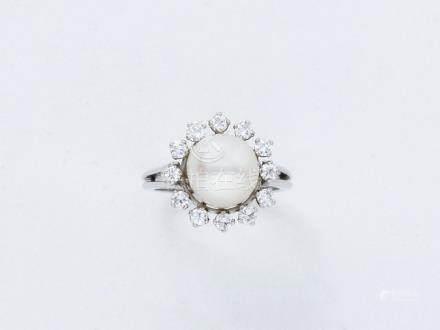 Bague en or gris 750 millièmes ornée d'une perle de culture entourée de diamant