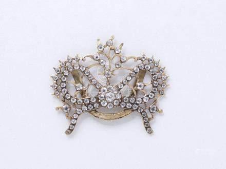Passant de ruban en or 750 millièmes, stylisant un nœud habillé de pierres du R