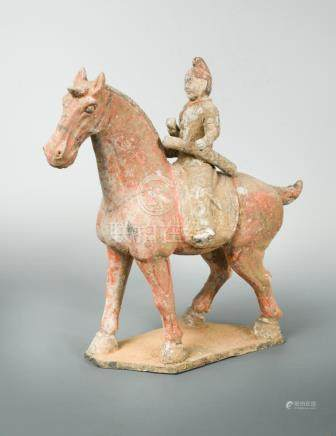 A painted pottery figure of a horse and rider, possibly Tang dynasty, the seated rider astride a