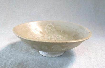 A Song dynasty shallow dish from a shipwreck, carved with stylised waves, the pale olive glaze