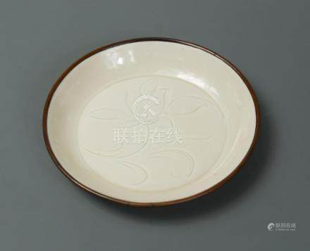 A Song dynasty small carved Ding ware dish, carefully moulded with a flat base and shallow