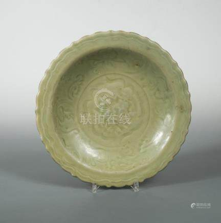 A Ming dynasty celadon barbed-rim dish freely carved to the interior with a peony medallion