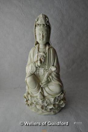 A blanc-de-chine figure of Guanyin holding a sceptre, seated on a lotus flower, 26cm.