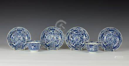 A pair of Chinese porcelain tea bowls and saucers, probably Kangxi period, of lotus form, the