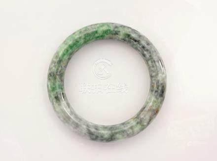 A carved jade bangle, believed to be Burmese, in mottled apple green, celadon and grey jade, 3¼