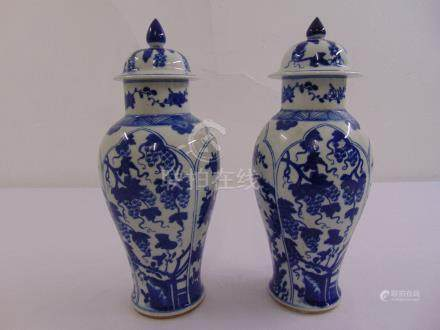 A pair of Chinese blue and white baluster vases with pull off covers decorated with flowers and