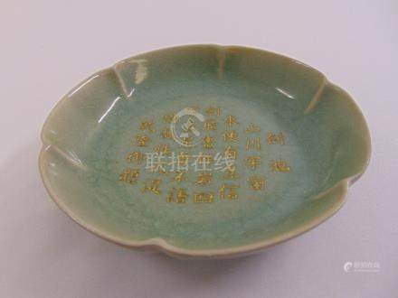 A Chinese celadon dish with scalloped edge and gilded Chinese characters