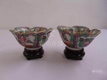 A pair of Chinese famille rose dishes with scalloped edges on hardwood stands