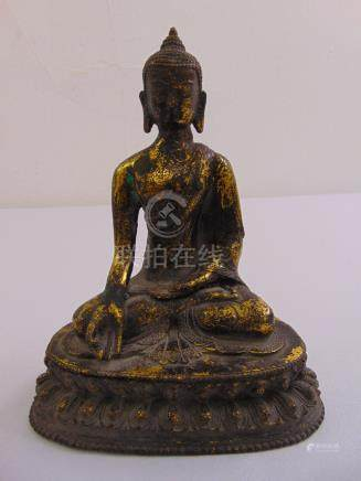 A Chinese gilded bronze figurine of Buddha on shaped oval base