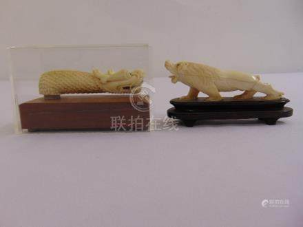 Two 19th century carved figurines a dragon in fitted case and a lion on wooden plinth