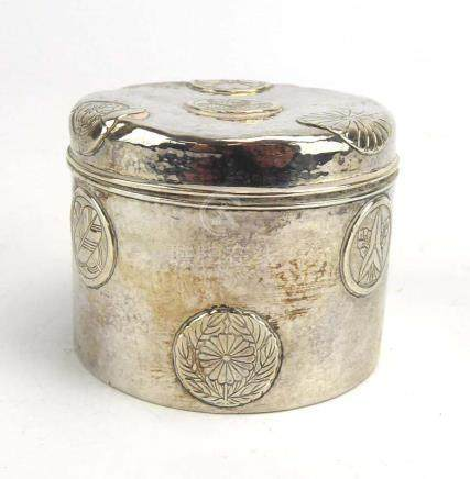 A Japanese metalware jar and cover of cylindrical form decorated with circular stylised flowerheads