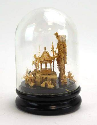 A carved cork figure modelled as a pagoda and a pair of cranes in a traditional landscape,