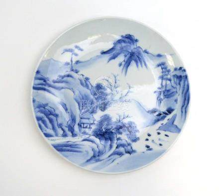 A Chinese blue and white charger decorated with a mountainous landscape, painted mark to base, d.