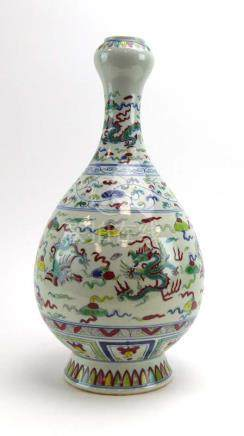 A Chinese vase of slender ovoid form decorated with stylised dragons on a white ground,