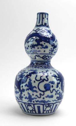 A Chinese blue and white double gourd vase, typically decorated with stylised dragons, h.