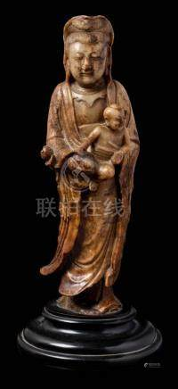 A Chinese carved soapstone figure of Guanyin: with chignon-tied upswept hair and wearing loose