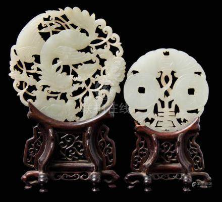 Two Chinese carved and pierced celadon jade discs: the larger in the form of a phoenix amongst