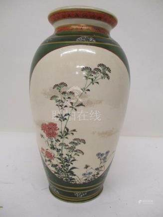A late 19th century Satsuma vase of baluster from decorated with two panels of flowers, on a green