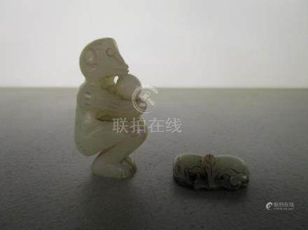 Two Chinese pale green jade carvings, probably 19th century, one a monkey squatting, holding a