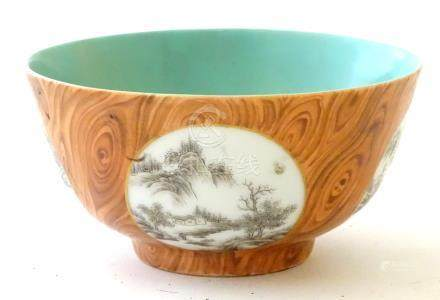 A Chinese tea bowl with four hand painted monochrome landscapes in roundels.