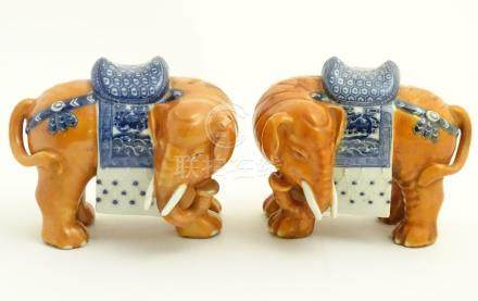 A pair of Chinese ceramic elephants with rust coloured bodies and blue and white patterned saddles.