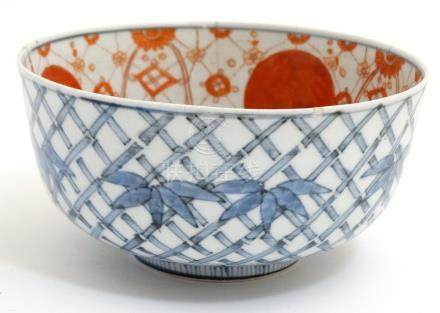 A Chinese blue and white bowl decorated with stylised bamboo and foliage to outer ,